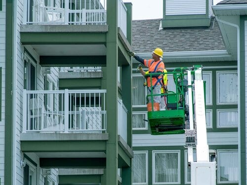 Painter on Sky jack painting balcony of high rise