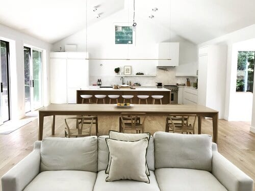 Layout of inside of house with a couch in the for front of two sets of kitchen tables